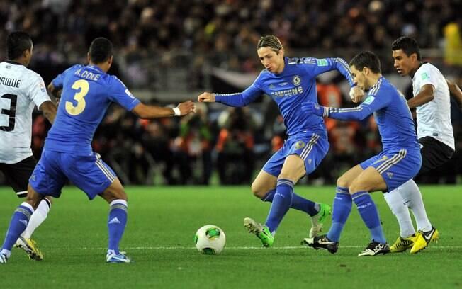 O espanhol Fernando Torres encara a marcação  de Jorge Henrique e Paulinho