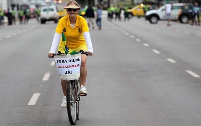 Em Brasília, uma mulher pedala sua bicicleta de camiseta do Brasil e um cartaz com os dizeres