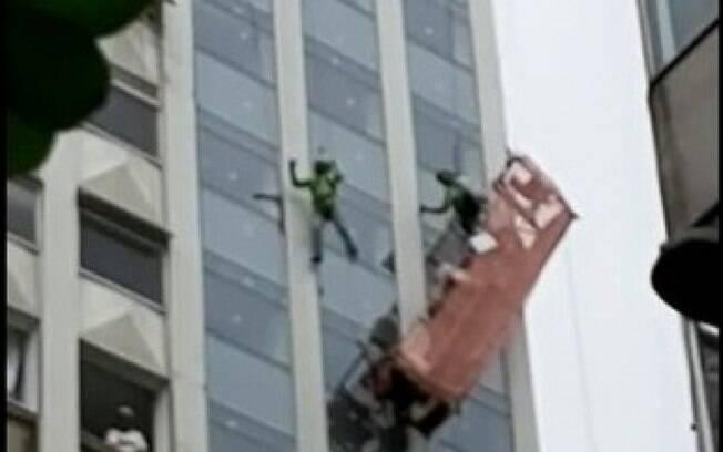 Operários pendurados em andaime