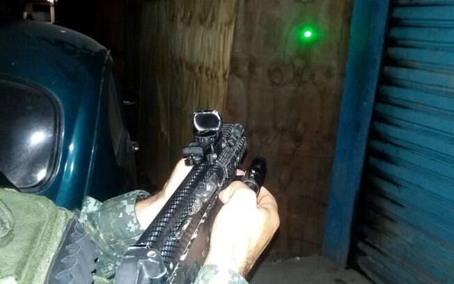 Submetralhadora 9mm usada pelos traficantes e apreendida pelo COE. O ponto verde na parede é emitido pela mira laser, indicando o local de impacto do tiro. Repare na pequena