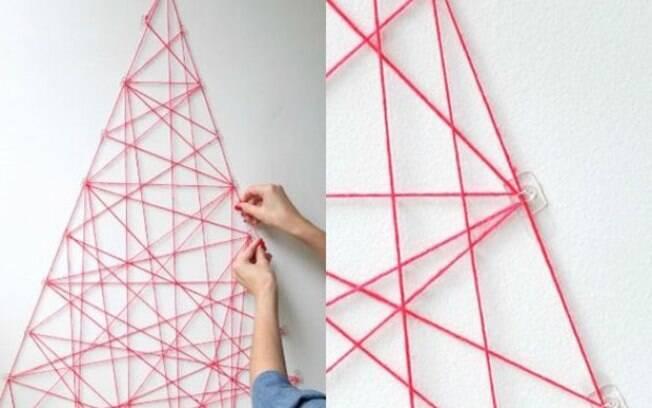 Bem geométrica, essa árvore super estilizada com linha vermelha e ângulos bem pensados pode ser uma opção para quem quer ocupar as paredes da casa no Natal