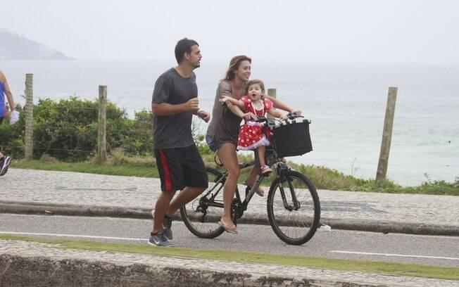 Dani Monteiro pedala com a filha, Maria,  na orla da Barra da Tijuca