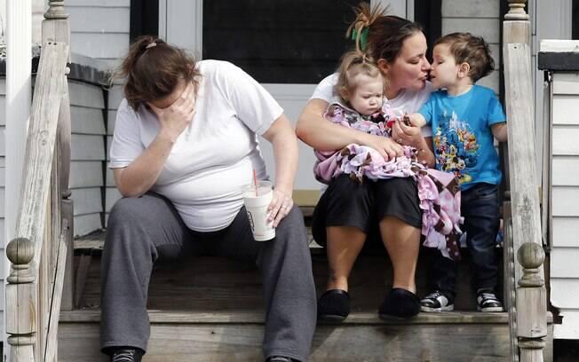 Vizinhos sentam do lado de fora de casa de pais de Krystle Campbell, que foi morta no ataque em Boston (16/04). Foto: AP