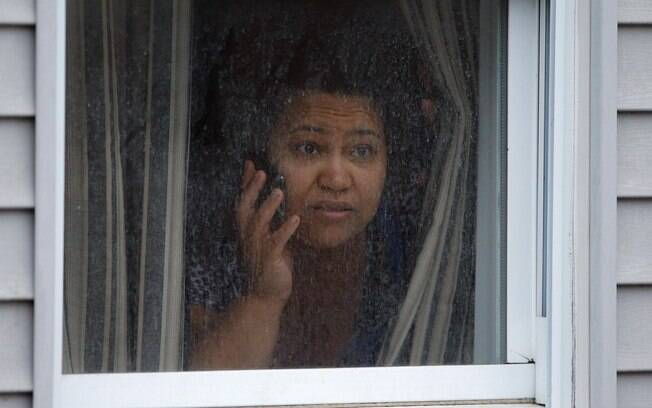 Mulher observa pela janela movimentação de policiais em busca de suspeitos no subúrbio de Watertown
