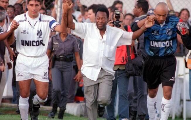 Pelé entra em campo com Gallo e Edinho, seu filho, antes de jogo do Santos na Vila Belmiro pelo Brasileirão de 1995. Foto: Gazeta Press