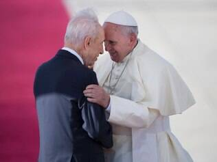 Pope Francis, right, talks with Israeli President Shimon Peres, during an official arrival ceremony at Ben Gurion airport near Tel Aviv, Israel, Sunday, May 25, 2014.  Pope Francis took a dramatic plunge Sunday into Mideast politics while on his Holy Land pilgrimage, receiving an acceptance from the Israeli and Palestinian presidents to visit him at the Vatican next month to discuss embattled peace efforts. The summit was an important moral victory for the pope, who is named after the peace-loving Francis of Assisi. Israeli-Palestinian peace talks broke down in late April, and there have been no public high-level meetings for a year. (AP Photo/Oded Balilty)