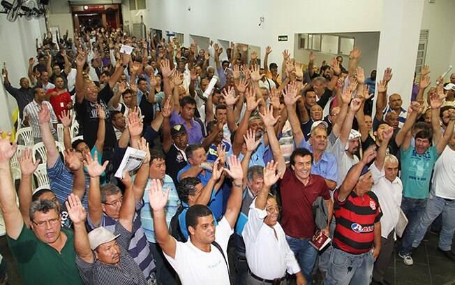 Funcionários da empresa levantam braços para confirmar apoio na paralisação, na semana passada