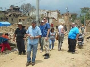 Sílvio (de camisa quadriculada) caminha entre escombros do primeiro terremoto; nova réplica  atingiu fortemente a capital do Nepal, Katmandu, nesta terça-feira (12)