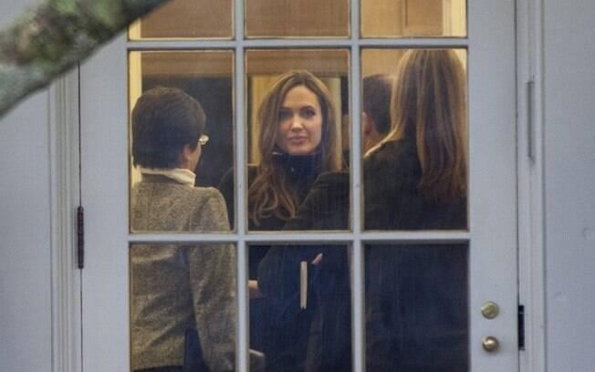Angelina Jolie é fotografada cercada de jornalistas na casa branca