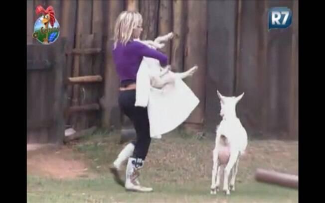 Com o filhote no colo, Anna Markun tenta tocar a cabra para o pasto