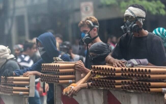 Manifestantes com rojões em frente à Alerj durante confronto com Batalhão de Choque