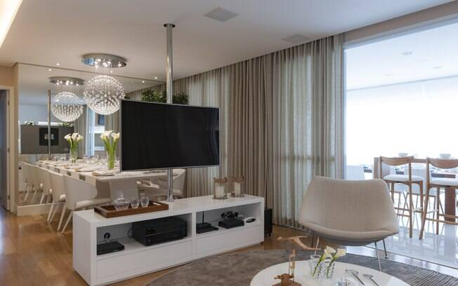 Apostar em televisores com suporte giratório permite usá-los nos ambientes integrados da sala de estar com a de jantar