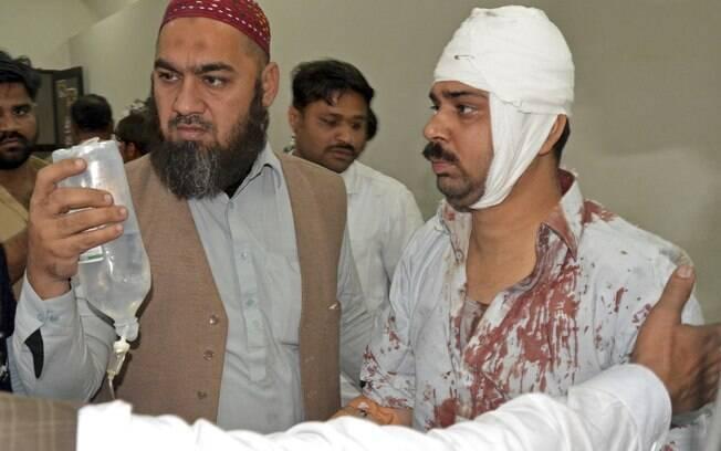 Paquistaneses ajudam vítima de explosão enquanto ela chega a hospital em Shikarpur, Paquistão