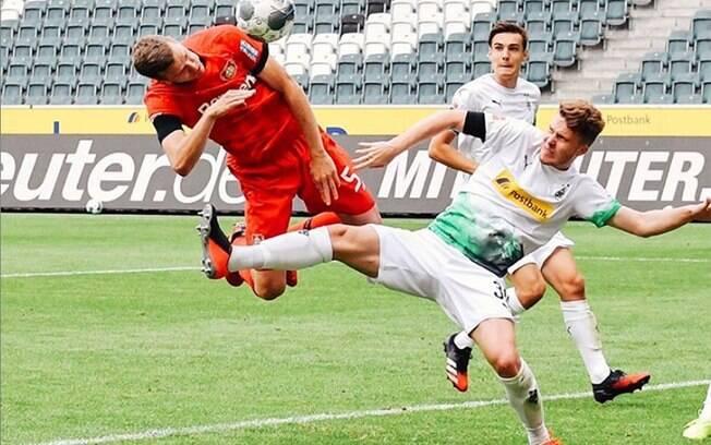 Jogador do Leverkusen disputa a bola na área