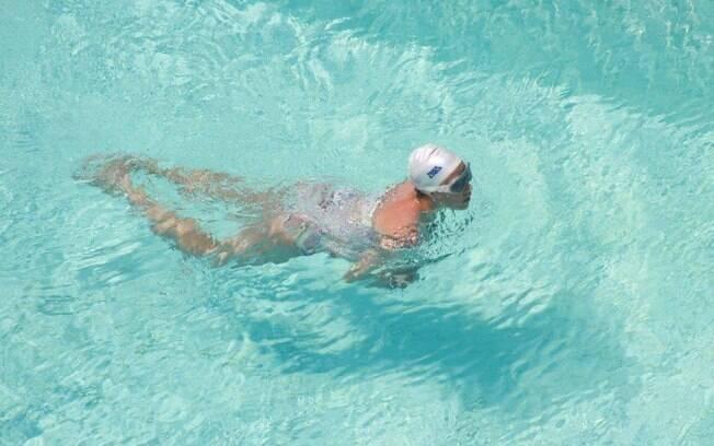 De óculos de natação e toca, Luana Piovani nada na piscina do Copa