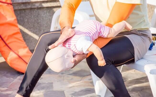 Quando crianças de até um ano ficam engasgada, o ideal é realizar a manobra com o bebê de bruços, como mostra a imagem