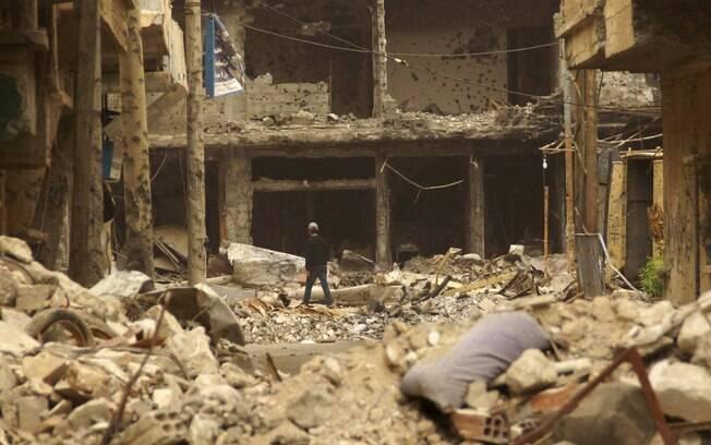 Residente caminha sobre destroços de prédios em rua de Deir al-Zor, Síria (09/05)