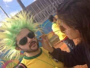 Com adereços e tintura verde e amarela no rosto, torcedor brasileiro exalta seleção nacional em dia de jogo em Brasília