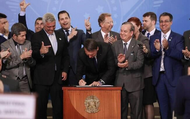 Presidente Jair Bolsonaro (PSL) assina decreto que muda regulamento para porte e posse de armas, enquanto senadores e deputados da base aliada comemoram