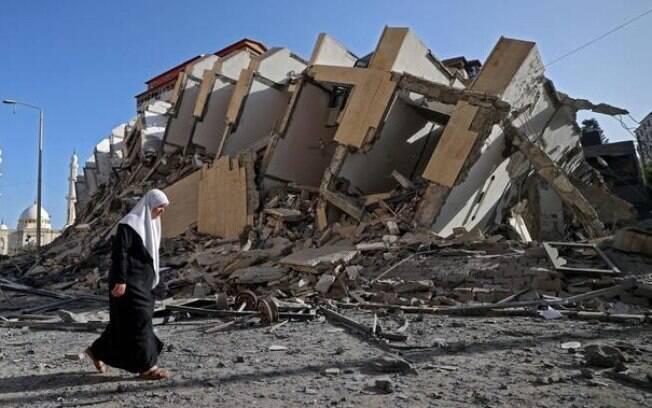 Mulher caminha ao lado dos destroços do prédio de 13 andares derrubado em Gaza por bombardeio Israelense