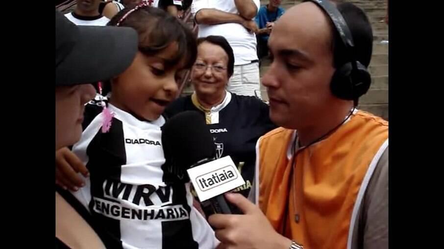 Rebeca Penna criança em entrevista a Itatiaia, em um jogo do Atlético-MG