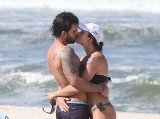 Juliano Cazarré beija a mulher, Letícia, na praia da Barra, no Rio