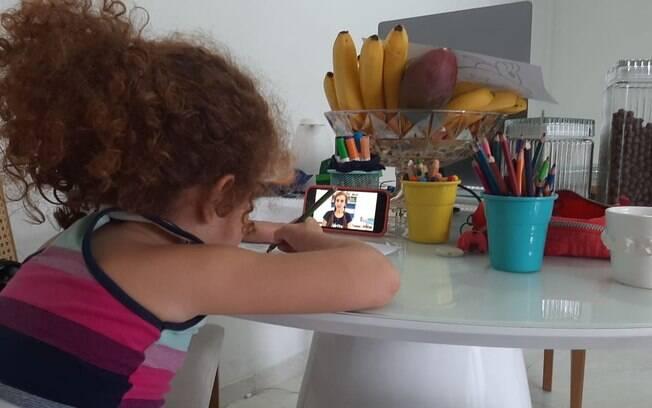 Olívia, que está no Jardim II, acompanha atividades pelo celular