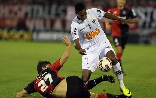 Jô tenta passar pela marcação de Santiago  Vergini em ataque atleticano