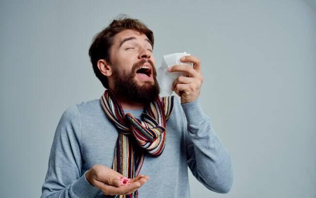 Homem espirrando com lenço próximo ao rosto
