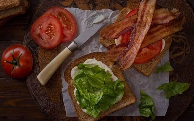 Alface, tomate e bacon dispostos em uma mesa.