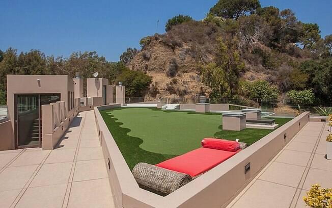 Para tomar um sol, a propriedade ainda tem um deck, com visão para a grande área externa