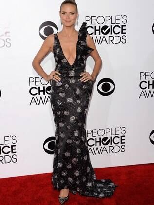 Heidi Klum escolhe vestido decotado, com brilho, bordados, calda e manga em alto relevo