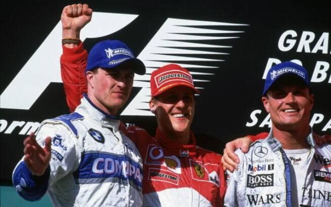 Os irmãos Michael (centro) e Ralf (esquerda) Schumacher comemoram dobradinha no GP do Brasil de 2002