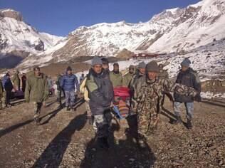 Soldados carregam vítima de avalanche antes de ser levada de helicóptero para Thorong La, Nepal (15/10)