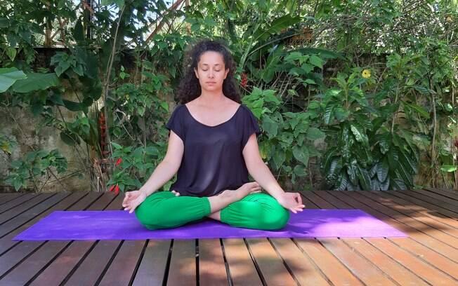 a instrutora de yoga juliana gontad está sentada em uma esteira roxa, em cima de uma estrutura de madeira; atrás dela está uma parede coberta de plantas
