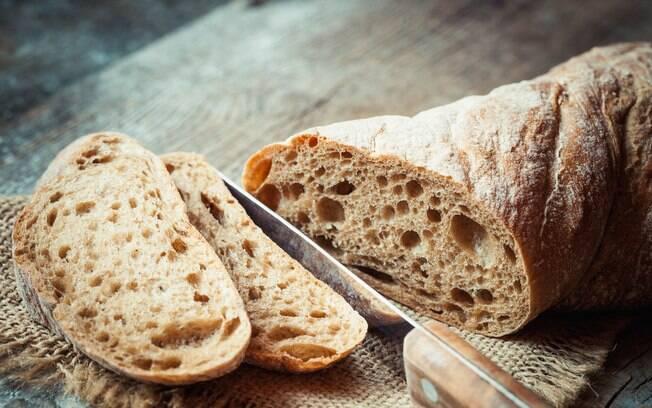 pão fatiado em uma tábua de madeira