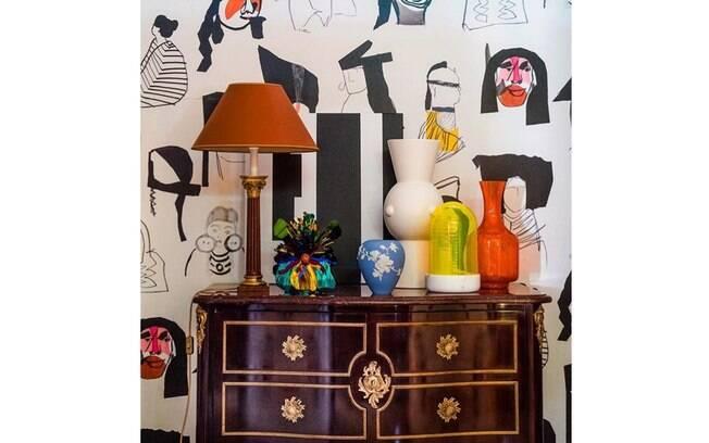 O aparador antigo conta com o papel de parede super contemporâneo e com objetos coloridos para criar o clima