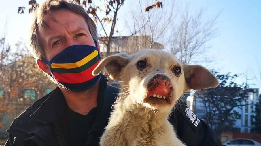 Paul Farthing posa com um dos cães da ONG Nowzad, de proteção aos animais