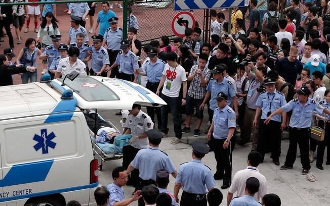 Feridos são atendidos diante da Tongji  University. Beckham cancelou a visita após o  tumulto