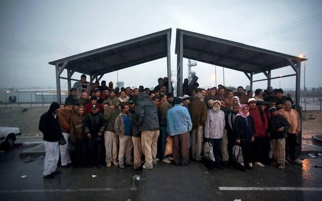 Trabalhadores palestinos se abrigam por causa da chuva enquanto esperam transporte depois de cruzar a fronteira para trabalhar em Israel (Arquivo)
