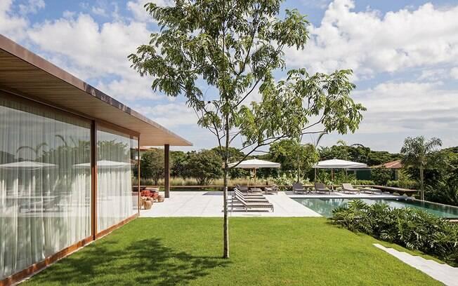 A casa tem 1.185 m² e é repleta de panos de vidros. As cortinas das janelas conseguem garantir privacidade aos moradores