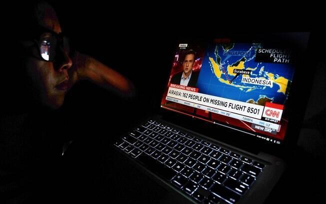 Mulher acompanha minuto a minuto notícias sobre o avião desaparecido. Foto:  Getty Images/Robertus Pudyanto