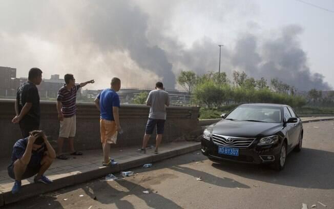 Moradores se reúnem perto do local onde houve explosão em um porto de Tianjin, China (13/08). Foto: AP