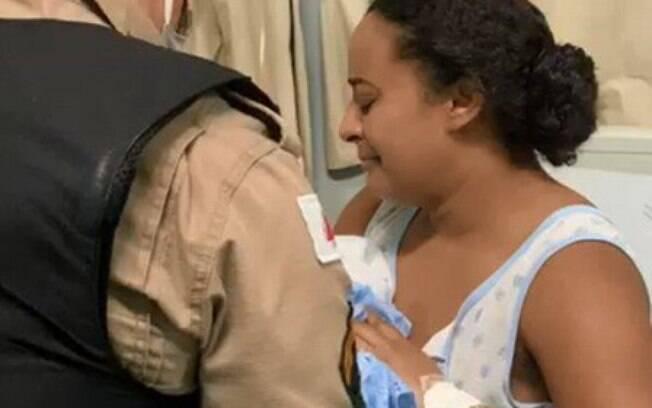 Momento em que a polícia devolve a criança para os braços da mãe, na zona da mata de Minas Gerais