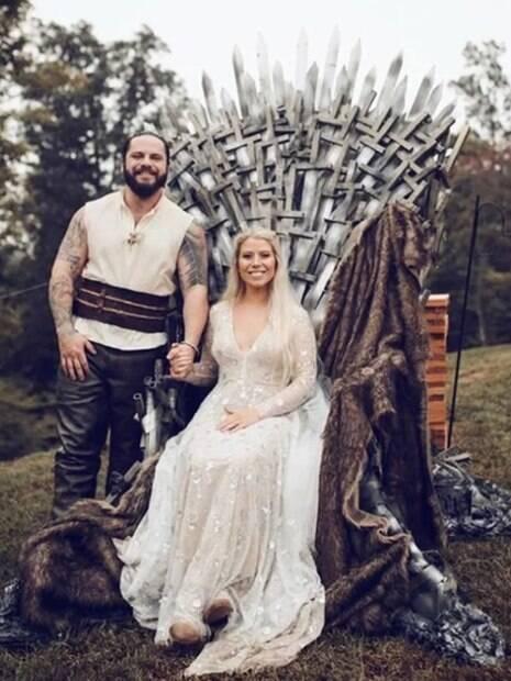 Casal sentado no Trono de Ferro de