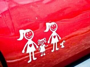 A família feliz na traseira do carro: duas mulheres, uma menina e um cachorro