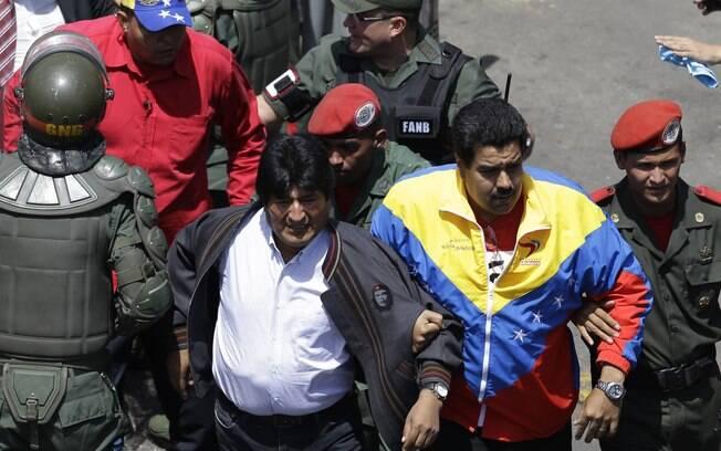 Vice-presidente da Venezuela, Nicolás Maduro (2º à D), segura braço de líder boliviano, Evo Morales, em Caracas (06/03)