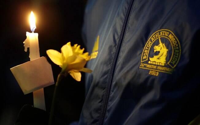 Lizzie Lee, 56, que participava de sua primeira Maratona de Boston, segura vela e flor durante vigília por vítimas de ataque (16/04). Foto: AP