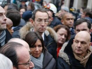 French President Francois Hollande (C) talks to the press after arriving at the headquarters of the French satirical newspaper Charlie Hebdo in Paris on January 7, 2015, after armed gunmen stormed the offices leaving eleven dead, including two police officers, according to sources close to the investigation.