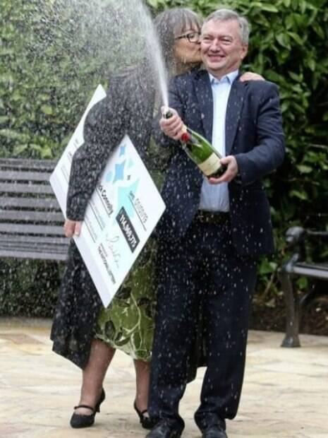 casal estourando champagne e segurando cheque